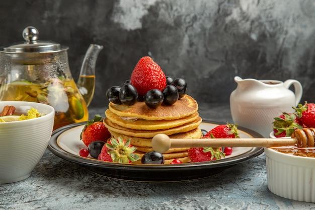 Frente panquecas deliciosas com frutas e chá na superfície clara de frutas doces café da manhã