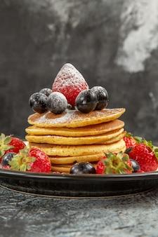 Frente panquecas deliciosas com frutas frescas na superfície clara café da manhã frutas doces