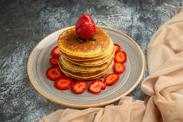 Frente panquecas deliciosas com morangos frescos em bolo de superfície clara de frutas doces