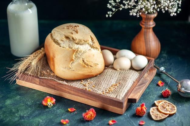 Frente pão fresco saboroso com ovos e leite na superfície escura