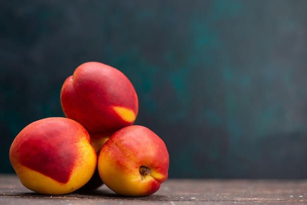 Frente pêssegos frescos deliciosas frutas doces em uma superfície azul escura suco de frutas suave verão fresco
