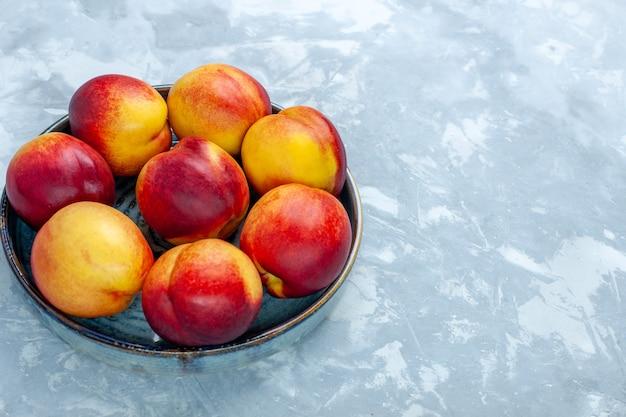 Frente pêssegos frescos deliciosos frutos de verão em uma mesa branca clara