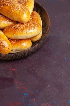 Frente rissóis doces deliciosas tortas assadas para chá na mesa escura