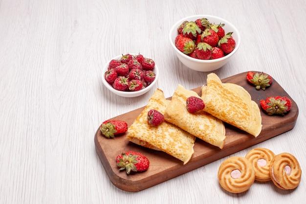 Frente saborosas panquecas doces com frutas no espaço em branco