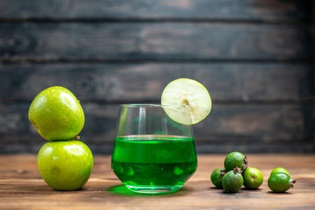 Frente suco de feijoa verde dentro de um copo com maçãs verdes na mesa de madeira