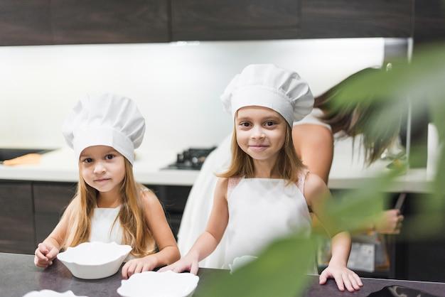 Frente, vista, de, dois, irmãos, ficar, perto, contador cozinha, desgastar, cozinheiro, chapéu, e, avental