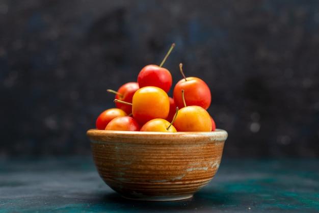 Frente vista de perto ameixas frescas frutas ácidas e maduras dentro de uma pequena panela no fundo azul escuro frutas suaves vitamina fresca