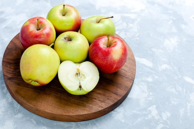 Frente vista de perto maçãs frescas frutas maduras maduras em branco-claro frutas mesa com vitamina cor foto