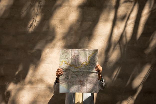 Frente, vista, pessoa, segurando, mapa, sobre, rosto