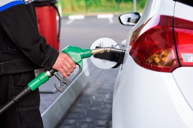 Frentista de posto de gasolina no trabalho. reabastecimento de carro em um posto de gasolina.