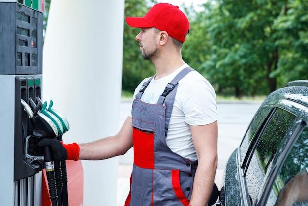 Frentista do posto de gasolina com um bico de combustível nas mãos, enchendo o tanque do carro do cliente