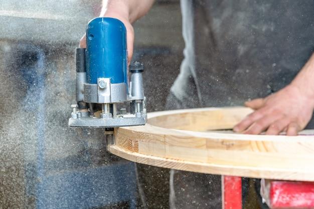 Fresamento da janela redonda de madeira usando cortadores elétricos de mão em marcenaria