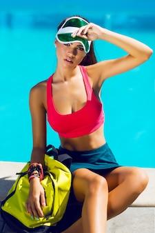 Fresca saudável atraente jovem vestida de esporte elegante, sentado perto da piscina em dia quente de verão. possui corpo bronzeado perfeito.