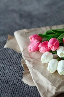 Fresco buquê de tulipas brancas e rosa sobre papel reciclado em fundo cinza