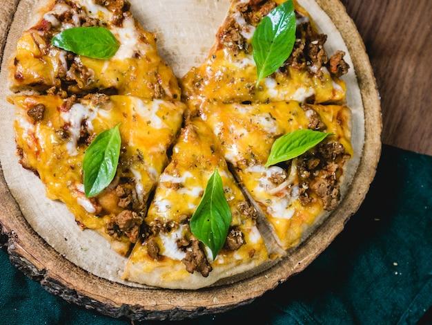Fresco cozido pizza crocante com queijo de carne e folhas frescas de manjericão