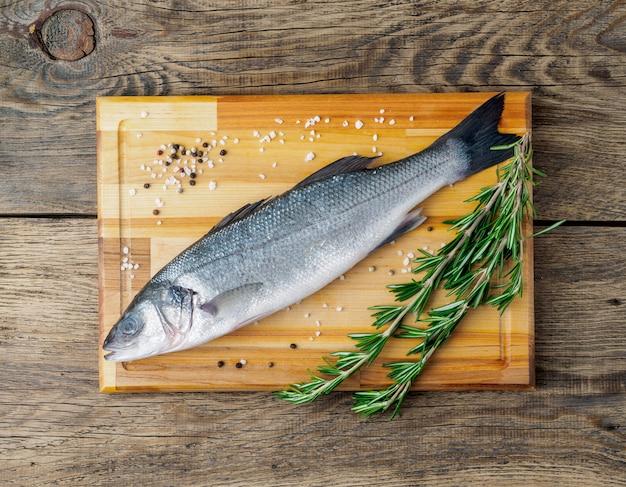 Fresco, cru, peixe de água salgada, robalo na tábua de madeira na velha mesa de madeira envelhecida, rústica