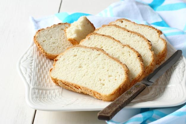Fresco do forno fatiado pão sem glúten na placa