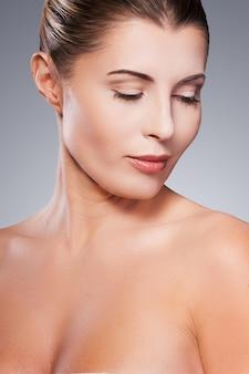 Fresco e bonito. retrato de uma mulher madura sem camisa, olhando para o ombro dela em pé contra um fundo cinza