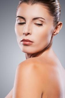 Fresco e bonito. vista traseira de uma mulher madura sem camisa, olhando por cima do ombro em pé contra um fundo cinza