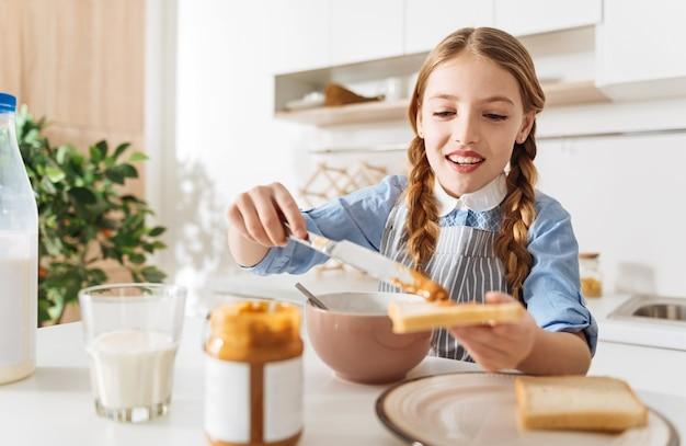 Fresco e saudável. menina bonita e animada, espalhando manteiga de amendoim saborosa sobre um pedaço de pão enquanto cozinha o café da manhã e usa um avental