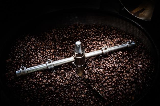 Fresco, grãos de café e máquina de cobertura de fiação torrado profissional fechar foto borrão e fundo escuro longa exposição tiro movimento conceito