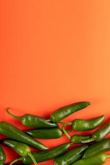 Fresco picante de pimenta verde em fundo laranja