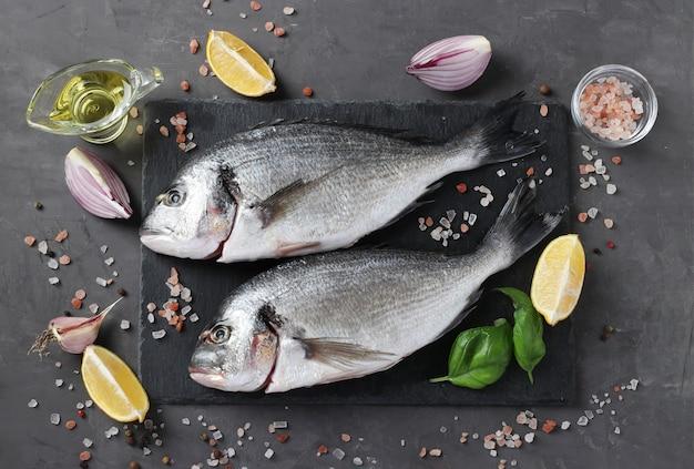 Fresco pronto para cozinhar dourado de peixe cru com ingredientes e temperos como manjericão, limão Foto Premium