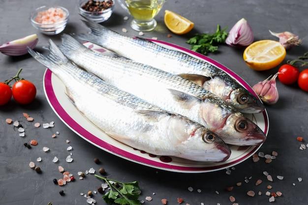 Fresco pronto para cozinhar salmonetes crus com ingredientes e temperos como salsa, limão, tomate cereja, cebola roxa e azeite em fundo escuro. fechar-se