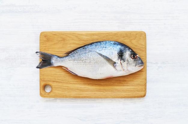 Fresco royal dorade no prato na tábua de madeira. fundo branco. conceito de comida saudável. vista superior, copie o espaço. conceito de frutos do mar do mediterrâneo.