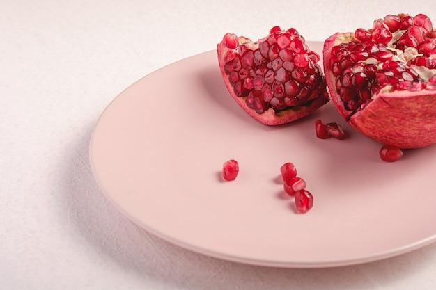 Fresco saboroso doce romã descascada com sementes vermelhas em chapa rosa sobre fundo branco, vista de ângulo, frutos de alimentos saudáveis