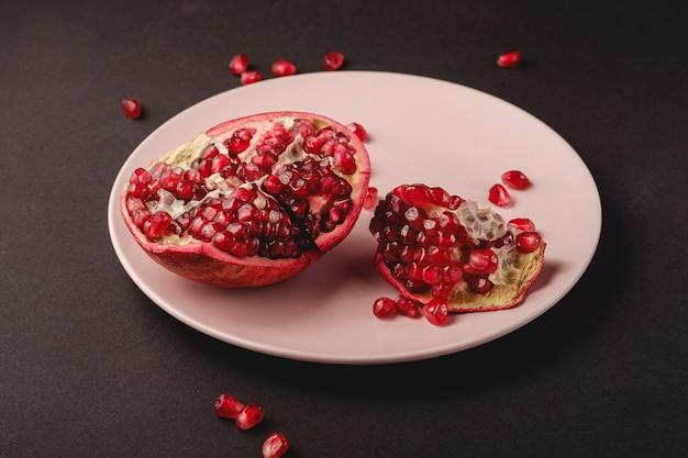 Fresco saboroso doce romã descascada com sementes vermelhas em chapa rosa sobre fundo preto escuro