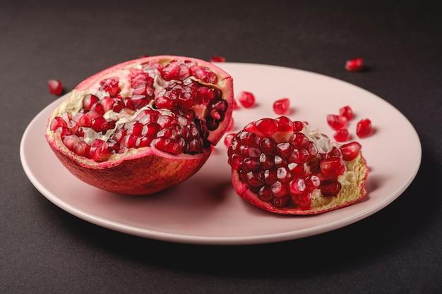 Fresco saboroso romã descascada doce com sementes vermelhas em chapa rosa sobre preto escuro