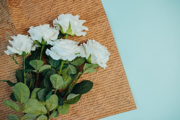 Frescor da primavera. rosas brancas com folhas verdes. lindas rosas brancas com haste longa no papel de papel kraft.