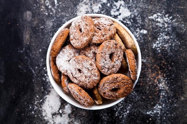 Fresh cozido biscoitos de chocolate e biscoitos de aveia com monte de açúcar em pó em tigela branca