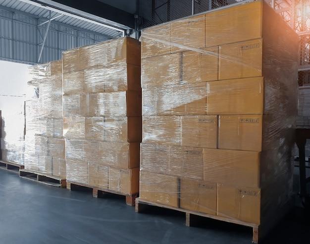 Frete de carga, expedição, serviço de armazenamento de entrega. pilha de caixas de papelão em paletes de madeira no armazém.