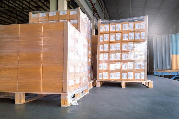 Frete de cargas, expedição, expedição, entrega, logística e transporte de cargas. grandes paletes esperando para serem carregados em um contêiner de caminhão.