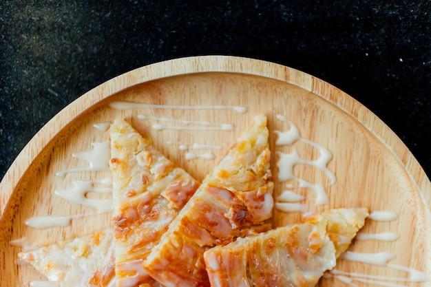 Fried roti com sobremesa de leite condensado servido em prato de madeira.