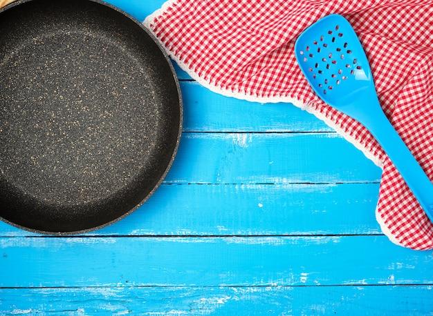 Frigideira antiaderente redonda preta vazia com alça em madeira azul