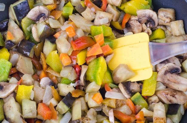 Frigideira com legumes fritos da estação e cogumelos em branco.