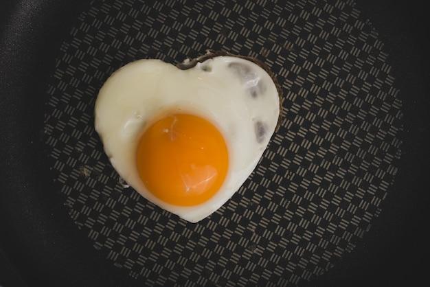 Frigideira com ovo frito com forma do coração