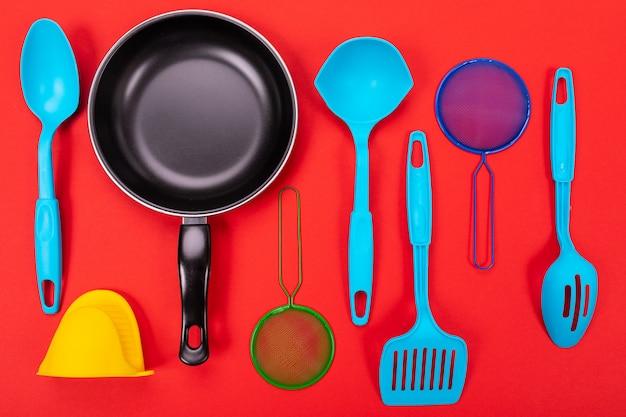 Frigideira com utensílios de cozinha, isolado no vermelho