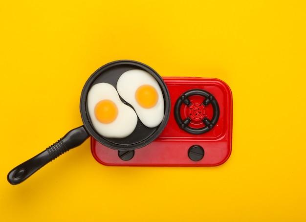 Frigideira de brinquedo em miniatura com ovos fritos no fogão. fundo amarelo. vista do topo. minimalismo. foto de estúdio