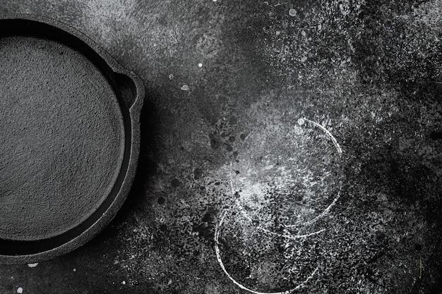 Frigideira de ferro fundido com espaço de cópia para texto ou comida com espaço de cópia para texto ou comida, vista de cima plana lay, em fundo preto de mesa de pedra escura