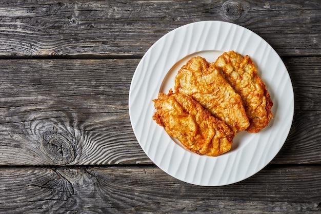 Frigideira de frango frito desossado, costeletas de peito de frango servidas em um prato branco sobre uma mesa de madeira rústica, vista de cima, horizontal, espaço livre