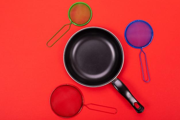 Frigideira no centro com utensílios de cozinha ao redor isolado no vermelho