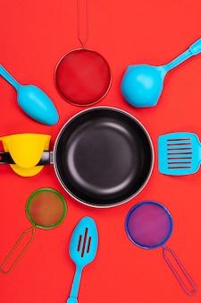 Frigideira no centro com utensílios de cozinha em vermelho