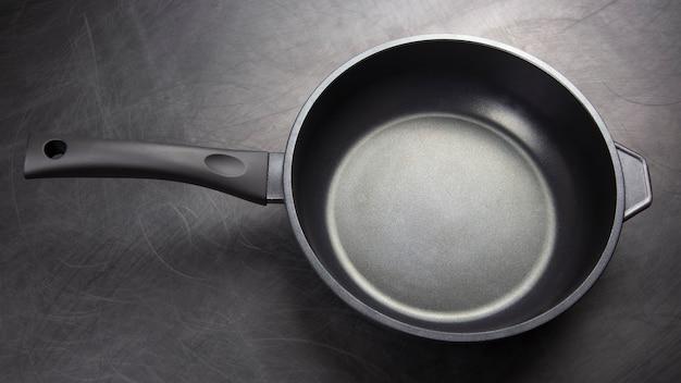 Frigideira preta com revestimento antiaderente de teflon em fundo escuro