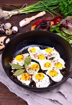 Frigideira preta de ferro fundido com ovos de codorna fritos