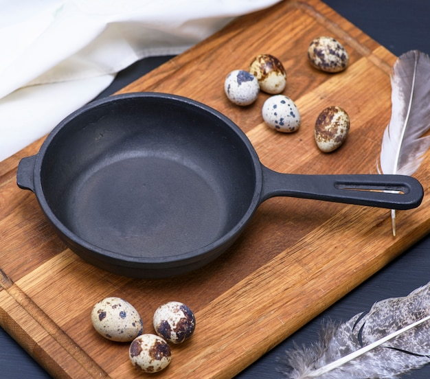 Frigideira preta vazia de ferro fundido e ovos de codorniz