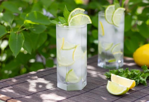 Frio refrescante limonada ou mojito cocktail em um copo em bambu cinza e verde deixa fundo
